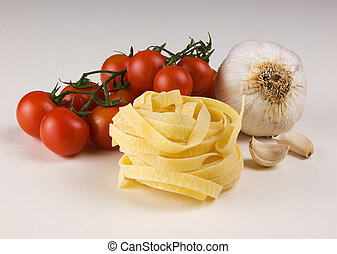 raw taglatelle tomatoes and garlic on white background