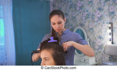 A professional hair stylist preparing beautiful bride before the wedding in a morning