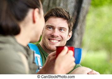 happy couple with cups drinking tea in nature - travel,...