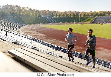happy couple running upstairs on stadium - fitness, sport,...