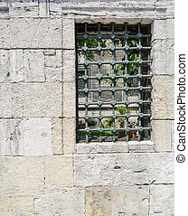 Old stone wall with window and grille - Old sandstone wall...