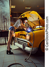 Sexy woman is welding something inside an old car
