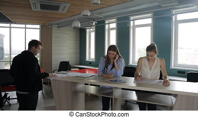Three persons stand near bar table and do working affairs....
