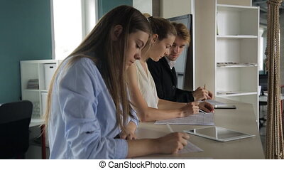 Three people stand near bar table in office and work
