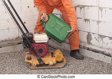 gasoline plate compactor - worker fills petrol into the tank...