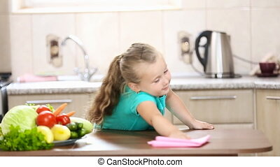 Little girl wiping the table in the kitchen