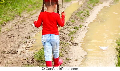 Girl launches a paper boat in a puddle of water