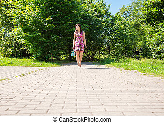 young woman goes barefoot on the sidewalk