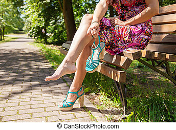 woman holding a shoe sitting on a park bench - young woman...