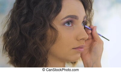 Professional makeup artist applying make up on a beautiful young face for a photoshoot