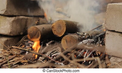 Burning wooden logs with smoke and fire. - Burning wooden...