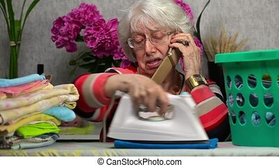 Ederly woman ironing and talking on smart phone