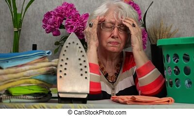 Ederly woman with headaches near ironing board