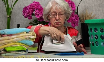 Old woman ironing and graded towels