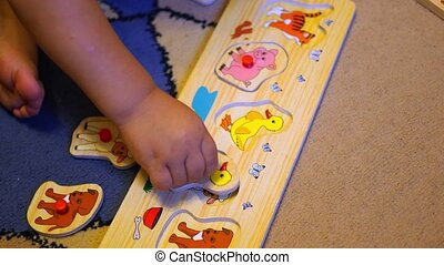 the child assembles a puzzle with animals