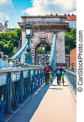 Tourists people with bicycles walking by chain bridge in...