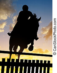 Silhouette of a rider on a horse jumping over obstacle at...