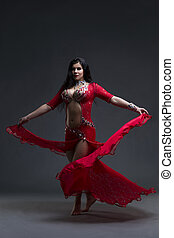 Young beautiful exotic eastern women performs belly dance in ethnic red dress