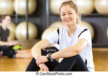 Workout portrait of a smiling woman at fitness center -...