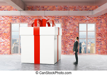 Businessperson looking at huge gift - Businessman looking at...