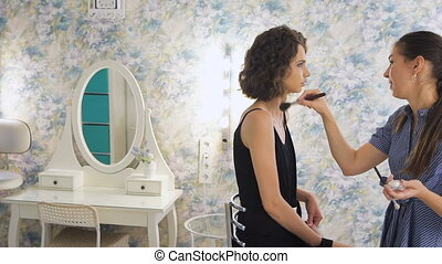Young female make-up artist working in the bright studio, applying makeup on a client