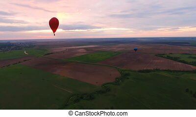 Hot air balloons in the sky over a fieldAerial view - Red...