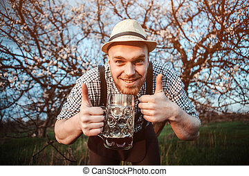 Happy smiling man with fresh brewed beer on the background...