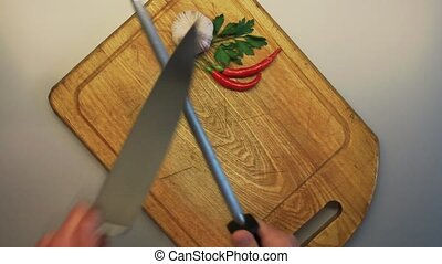 Male hands sharpening a knife against a background of an old wooden cooking board