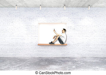 Guy on built-in-wall seating - Young man with smartphone on...