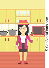 Young woman with apple in the kitchen.