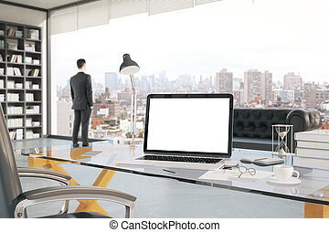 Businessman in office interior with blank white laptop,...