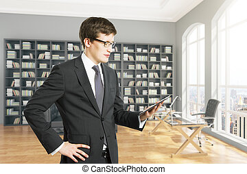 Businessman using tablet in library