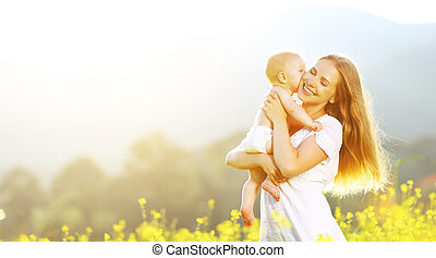 happy family mother and baby hugging and kiss in summer on nature