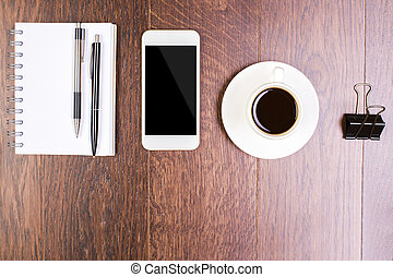 Smartphone, coffee and stationery - Top view of wooden...