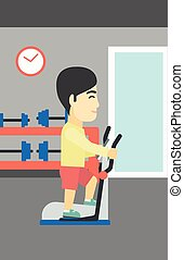 Man exercising on elliptical trainer - An asian young man...