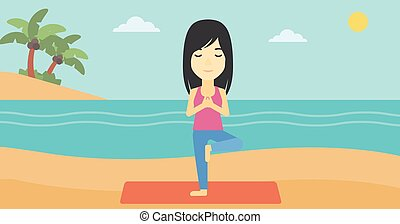 Woman practicing yoga tree pose on the beach.