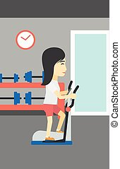Woman exercising on elliptical trainer. - An asian young...