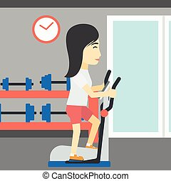 Woman exercising on elliptical trainer - An asian young...
