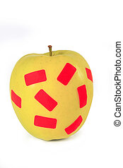 a yellow apple with stickers