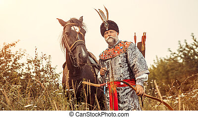 Medieval nobleman with the bow in one hand and horse strap...