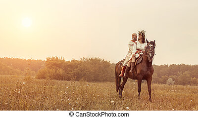 Mature man and woman in ethnic clothes are riding a horse on...