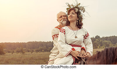 Mature man and woman are riding a horse on the rural summer...