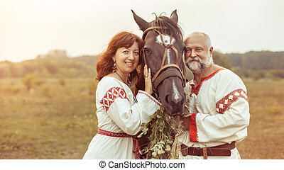 Mature man and woman in ethnic clothes are posing with the...