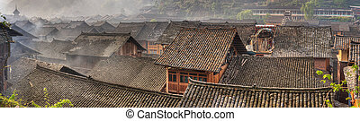 Morning fog over tiled roofs of peasant houses in chinese...
