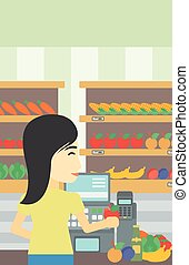 Cashier standing at the checkout in supermarket - An asian...