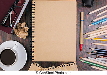Brown notepad and pencils - Top view of wooden desktop with...