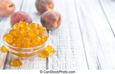 Gummy Peaches (detailed close-up shot) on an old wooden...
