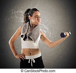Sweat and toil at gym - Woman raises a dumbbell weight...