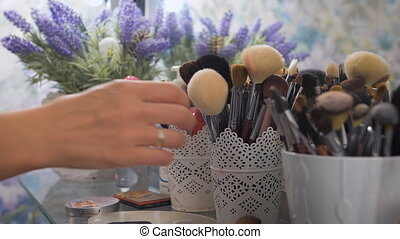 Makeup brushes, next to blue flowers, closeup - Beauty...