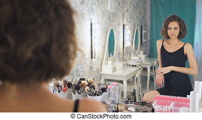 A beautiful young lady looking at a mirror enjoying herself.